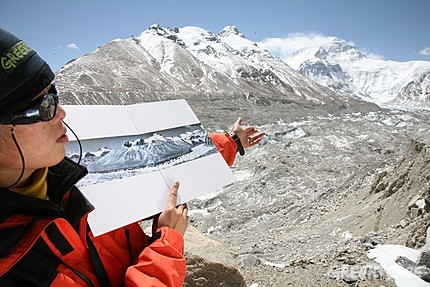 Climate change has caused dramatic glacial retreat. This is Rongbuk glacier in Tibet in 2007.The photo held by our Greenpeace staff is of the same glacier taken in 1968.
